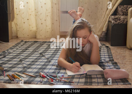 Girl teen who spend time at home drawing while lying on the floor - Stock Photo