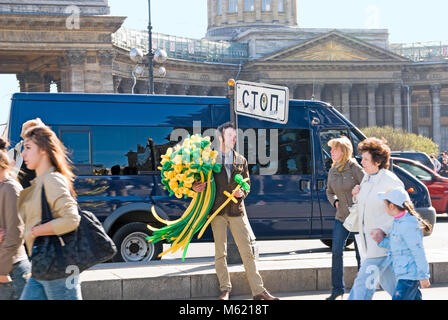 SAINT-PETERSBURG, RUSSIA, MAY 14, 2011: A smiling young man sells balloon flowers under the sign 'Stop' on Nevsky - Stock Photo