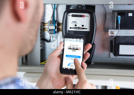 Close-up Of A Man's Hand Holding Mobile Phone Reading Electric Meter - Stock Photo