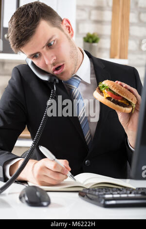 Young Business Man At Desk Eating Burger And Working At Workplace - Stock Photo