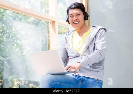 Chinese young man wearing casual clothes while using a laptop - Stock Photo