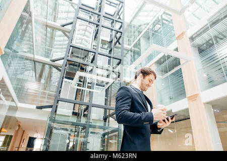 confident man holding coffee cup and using his smart phone while walking in hall - Stock Photo