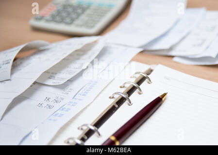 Checking receipt. Finance concept with receipts, calculators, and notes. Defocused. - Stock Photo