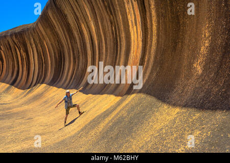 A sporty man enjoying surfing on the Wave Rock, a natural rock formation that is shaped like a tall breaking ocean - Stock Photo