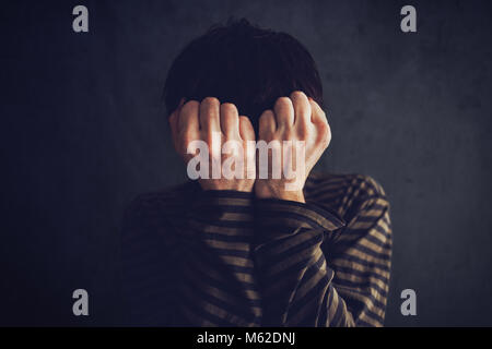 Distraught state of mind, depressive and sad man in dark room - Stock Photo