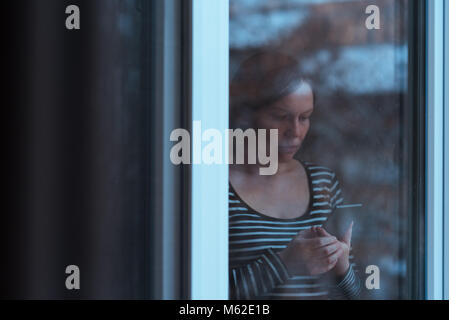 Alone sad man using mobile phone to send text message by the window in winter afternoon while it is snowing outside, teal and orange toned image with