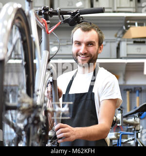portrait of a friendly and competent bicycle mechanic in a workshop repairs a bike - Stock Photo