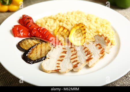 Grilled chicken with slices, with vegetables, bulgur on a white plate. In the background, lettuce leaves, color - Stock Photo