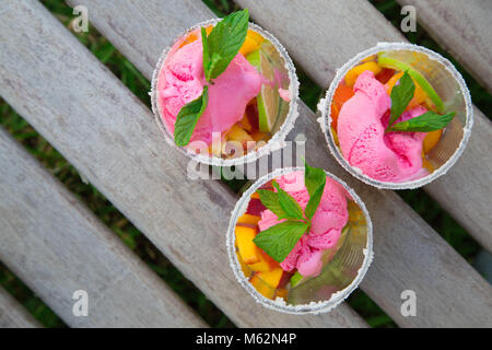 Three glasses with fruit salad and strawberry ice cream on the wooden surface. Free space for a text.Top view - Stock Photo