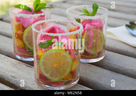 Three glasses with fruit salad and strawberry ice cream on the wooden surface. Spoons in the background - Stock Photo