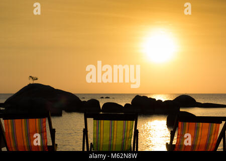 Three empty beach chairs facing the sea at sunset with silhouette of rocks over water and single tree on top of - Stock Photo