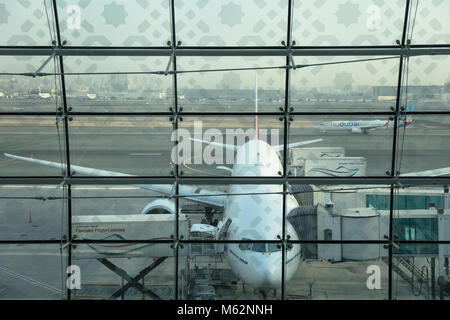 An airplane waiting for take off parked in the Dubai International airport, United Arab Emirates. - Stock Photo