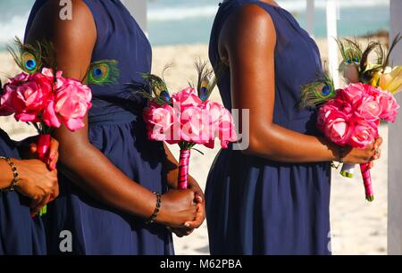 Three bridesmaids in dark blue dress holding pink bouquets at wedding on the beach in Cancun, Mexico. African American - Stock Photo