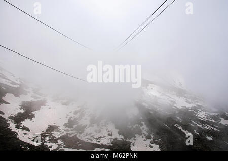 Car cables under cloudy weather on the way up to the Aiguille du Midi, near Chamonix. A famous ski resort at the - Stock Photo