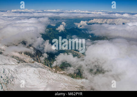Snow, glacier and Chamonix Valley, viewed from the Aiguille du Midi, near Chamonix. A famous ski resort at the foot - Stock Photo