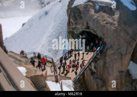 Footbridge between rocky peaks with tourists on the Aiguille du Midi, near Chamonix. A famous ski resort at the - Stock Photo