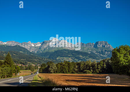 Road among fields, green forest and alpine landscape in a sunny day, near Saint-Gervais-Les-Bains. A famous ski - Stock Photo