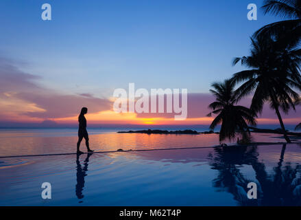 Woman silhouette walking over infinity pool at sunset in the island of Koh Phangan, Thailand. Vacation resort, tropical - Stock Photo