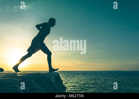 Man on the edge of a cliff about to jump into the sea on sunset in Koh Phangan island, Thailand. No fear concept. - Stock Photo