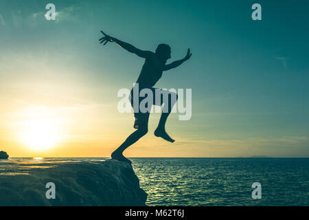 Man jumping over a cliff into the sea on sunset in Koh Phangan island, Thailand. Vintage effect. Dare, fearless - Stock Photo
