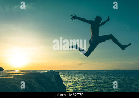 Man jumping over a cliff into the sea on sunset in Koh Phangan island, Thailand. Vintage effect. Three out of three - Stock Photo