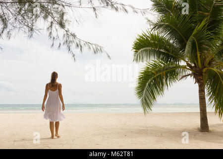 Lonely woman in white dress on the beach near a palm tree on an empty island in Thailand. Exotic, tropical vacation - Stock Photo