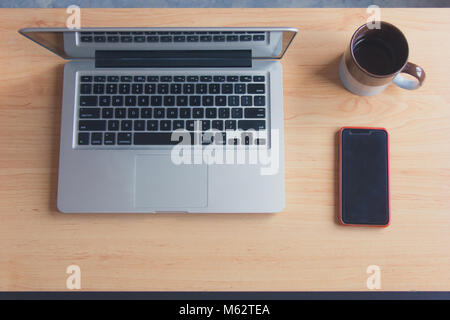 Grey laptop open next to coffee mug and cell phone from top. Home desktop. Ready to start working concept. Vintage - Stock Photo