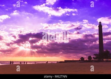 Scenic landscape in Maspalomas lighthouse with colorful sunset and silhouettes of people walking on the beach, Canary - Stock Photo