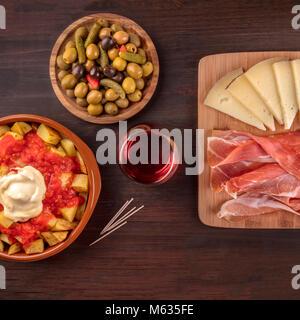 Tapas and wine. Patatas bravas, olives, jamon, cheese, square photo - Stock Photo