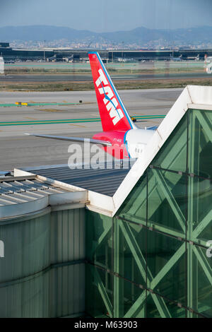 plane reflected in a terminal building while another airliner taxis past, Barcelona Airport - Stock Photo