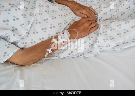 Soft focus intravenous line in a patient's hand - Soft focus hand of the old man with IV line on the bed in hospital - Stock Photo
