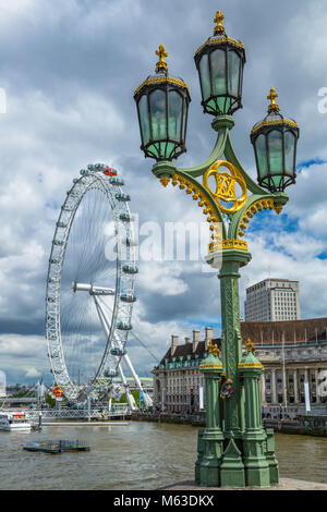 Street lamps on Westminster Bridge and the London Eye. - Stock Photo