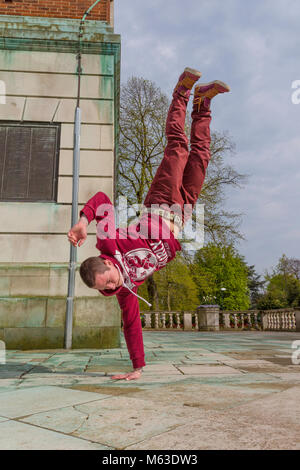 Breakdancer practicing in a public park. - Stock Photo