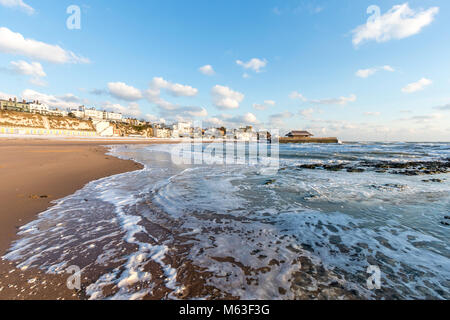 England, Broadstairs. Rough seas on the income tide at the beach at Viking Bay. Harbour in background. Bright sunshine. - Stock Photo