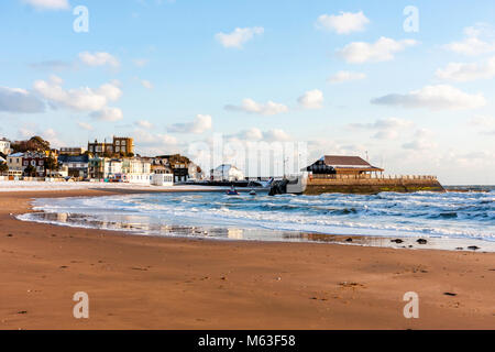 England, Broadstairs. Rough seas on the income tide at the beach at Viking Bay. Harbour in background. Bright sunshine - Stock Photo