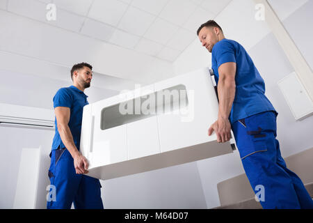 Two Smiling Young Male Movers Holding Furniture In Living Room - Stock Photo