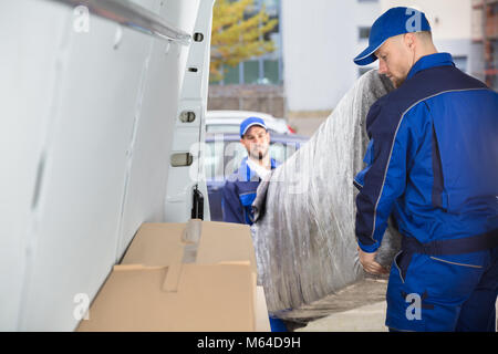 Two Happy Male Movers In Uniform Unloading Furniture From Truck - Stock Photo