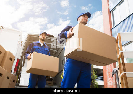Close-up Of Two Young Delivery Men Carrying Cardboard Box In Front Of Truck - Stock Photo
