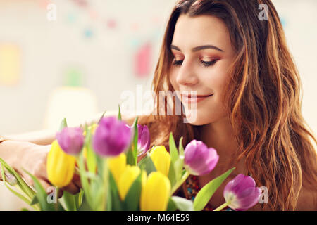 Attractive woman arranging tulips flowers in vase - Stock Photo