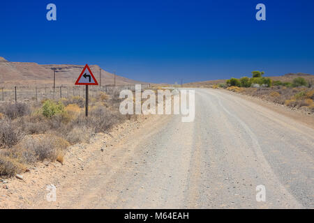 Desert landscape view of a sharp left turn sign on a dirt road in the Karoo of South Africa - Stock Photo