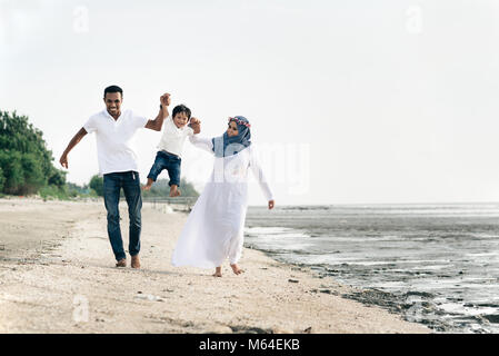 happy family having fun at muddy beach located in pantai remis,Selangor,Malaysia. Family concept - Stock Photo