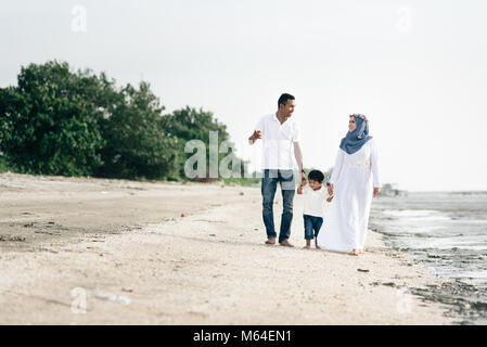 happy family having fun time walking together at the beach located in Pantai Remis,Kuala selangor,selangor,malaysia. - Stock Photo
