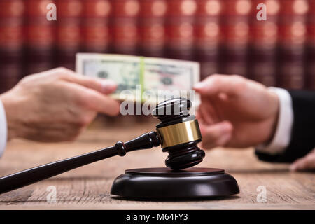 Judge Taking Bribe From Client Behind Gavel On Wooden Desk - Stock Photo