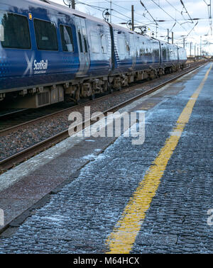 Close up of ScotRail local commuter train at Drem railway station in Winter with salt on station platform, East - Stock Photo