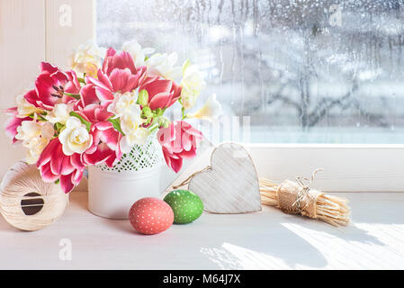 Pink tulips and white freesia flowers with Easter decorations on the window board, sunshine after rain - Stock Photo