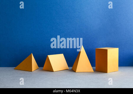 Abstract geometric figures. Three-dimensional pyramid tetrahedron cube rectangular objects on blue gray background. - Stock Photo