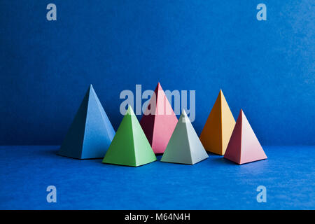 Platonic solid geometric figures. Three-dimensional pyramid rectangular objects on blue background. Yellow blue - Stock Photo