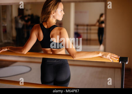 woman dancer posing near barre in ballet studio. - Stock Photo