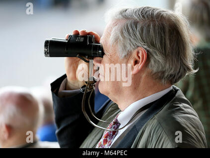15.04.2015.  Cheltenham, England. Cheltenham April Meeting Day One. A racegoer watches the race through binoculars - Stock Photo