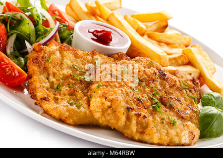 Fried pork chop, French fries and vegetables isolated on white background - Stock Photo